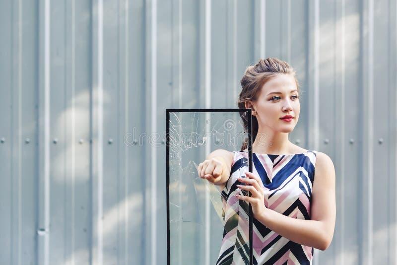 Bella ragazza teenager che tiene vetro rotto in sue mani Femminismo di concetto fotografia stock libera da diritti