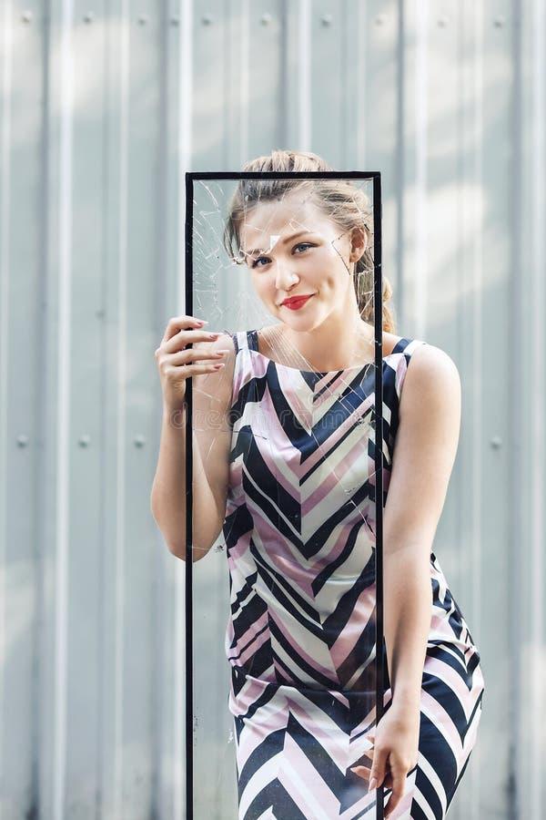 Bella ragazza teenager che tiene vetro rotto in sue mani Femminismo di concetto immagine stock