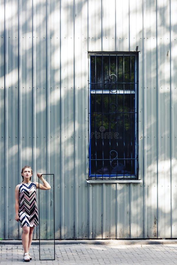 Bella ragazza teenager che tiene vetro rotto in sue mani Il concetto di adolescenza complessa fotografia stock
