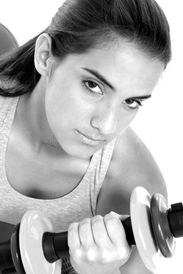 Bella ragazza teenager nei vestiti di allenamento e nei pesi della mano fotografia stock
