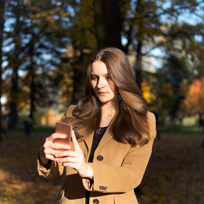 Bella ragazza teenager nel parco, tenendo smartphone e chatti fotografie stock