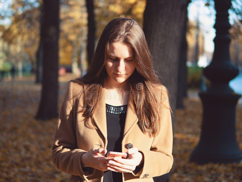 Bella ragazza teenager nel parco, tenendo smartphone e chatti fotografia stock