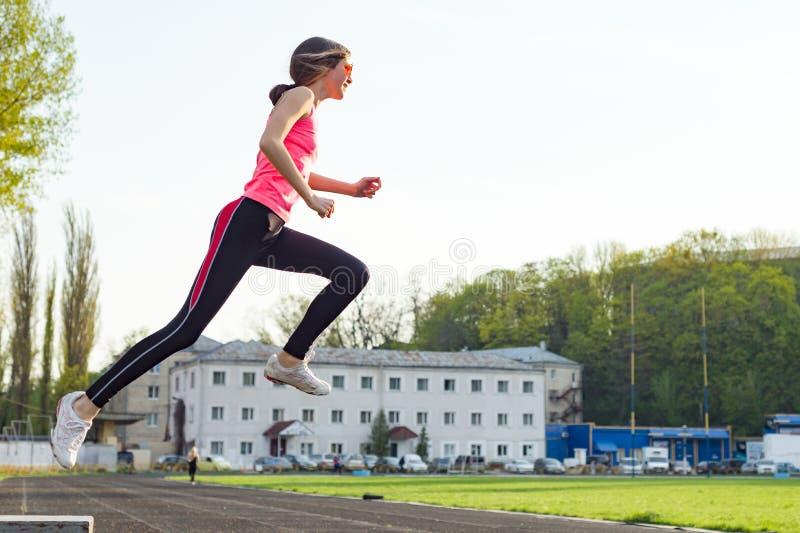 Bella ragazza teenager in vestiti di sport fotografati nel salto allo stadio fotografia stock libera da diritti