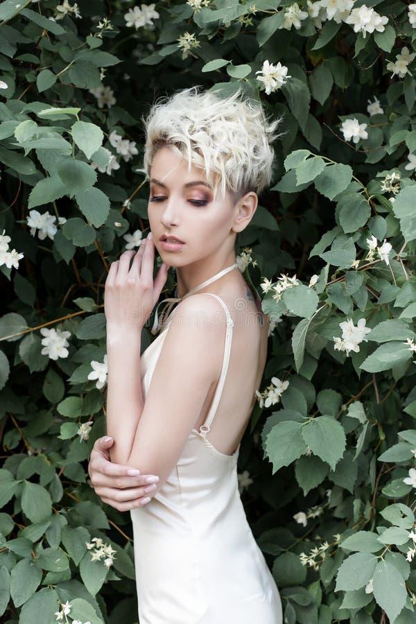 Bella ragazza tenera sexy con breve taglio di capelli in vestito crema con il fiore del gelsomino fotografia stock