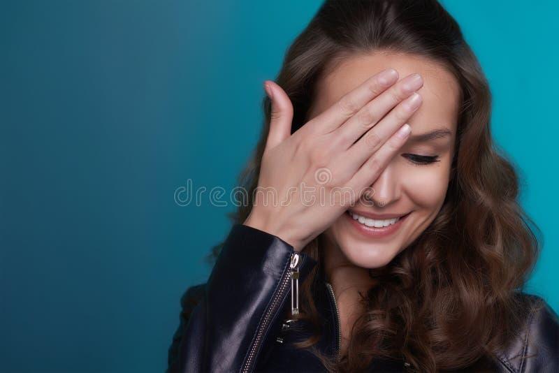 Bella ragazza timida con il sorriso brillante su un fondo blu fotografia stock