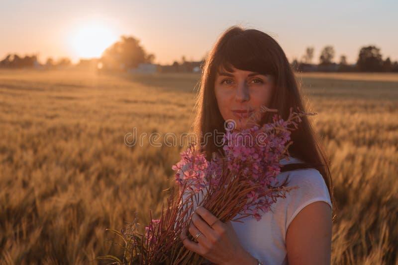 Bella ragazza in un campo con i fiori fotografia stock libera da diritti