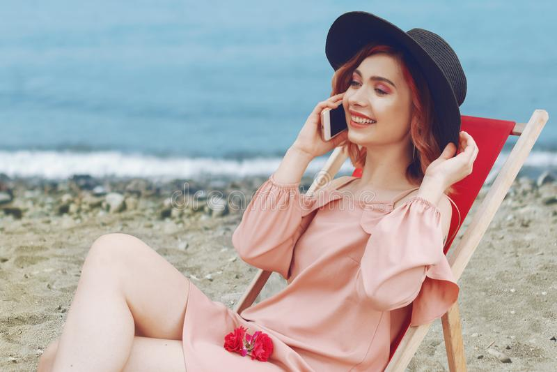 Bella ragazza in un cappello con capelli rosa e bello trucco che si trovano su una chaise-lounge contro la spiaggia e l'oceano fotografie stock libere da diritti