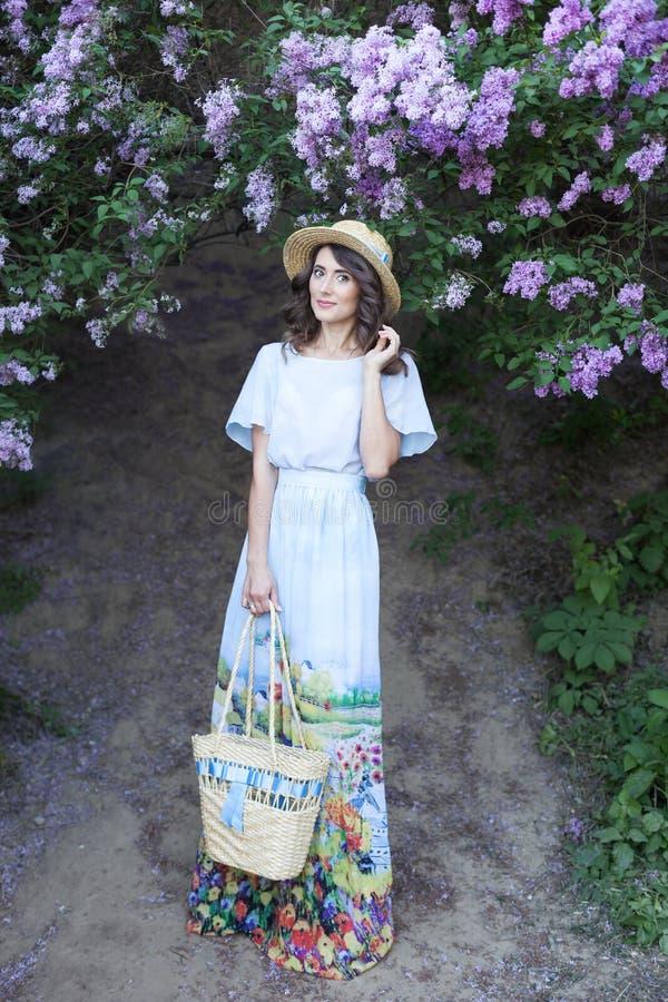 Bella ragazza in un cappello di paglia in un giardino lilla Ragazza con i fiori lilla nel tempo di primavera Giardinaggio Il conc fotografia stock libera da diritti