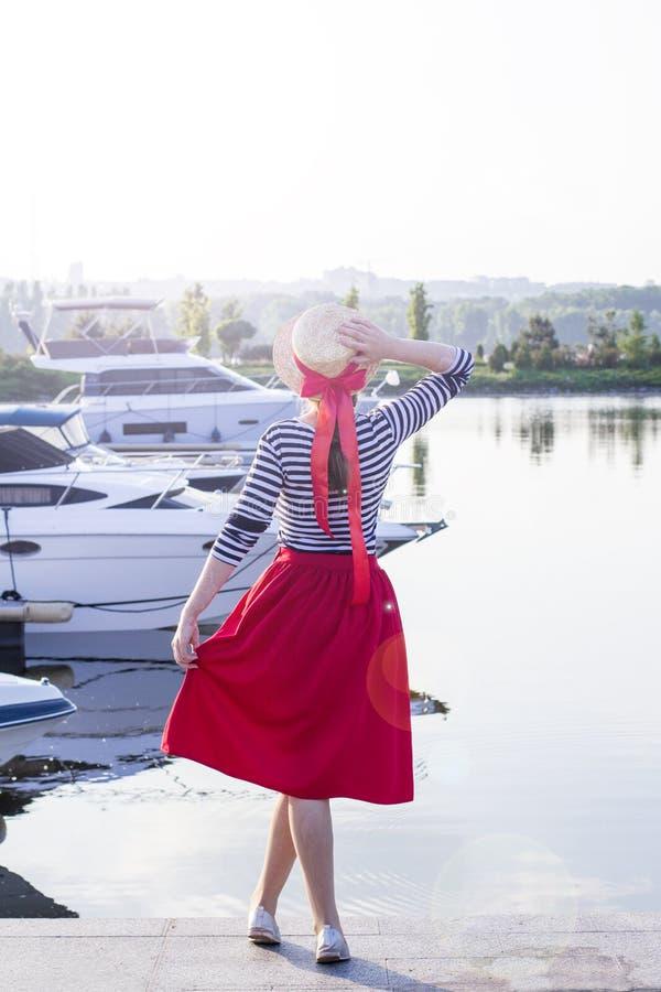 Bella ragazza in un cappello di paglia sul pilastro vicino agli yacht ed alle barche del mare Ragazza in una gonna rossa e un ves immagine stock