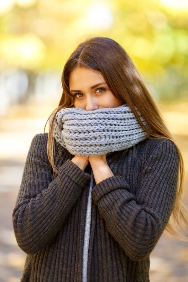 Bella ragazza in un cappotto nero su un fondo del parco di autunno fotografia stock libera da diritti