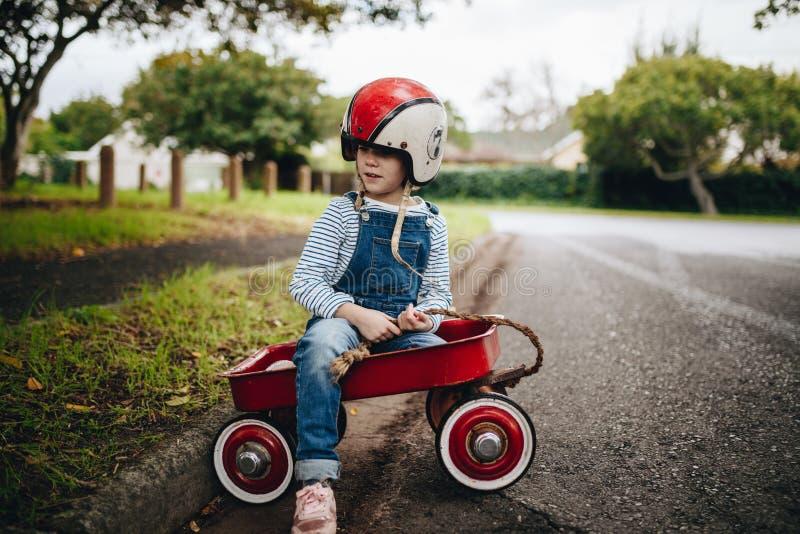 Bella ragazza in un carretto rosso del vagone fotografia stock