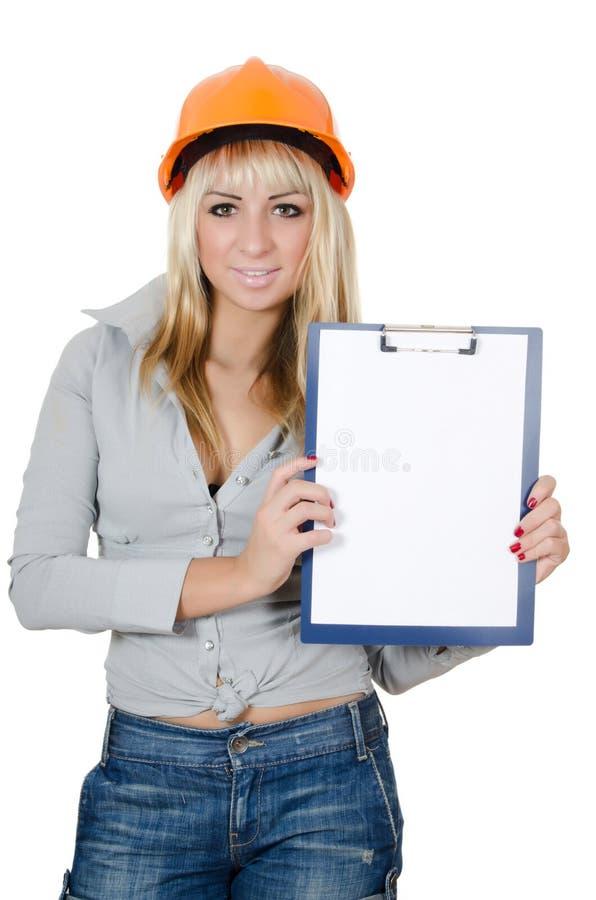 Bella ragazza in un casco della costruzione con i appunti immagini stock