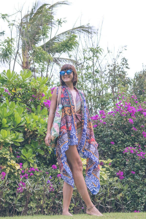 Bella ragazza in un costume da bagno e in un pareo che posano sul fondo del fiore in natura dell'isola di Bali, Indonesia immagine stock libera da diritti