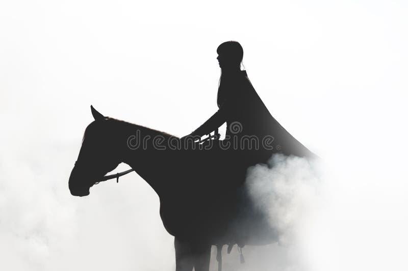 Bella ragazza in un impermeabile a cavallo nel fumo fotografie stock
