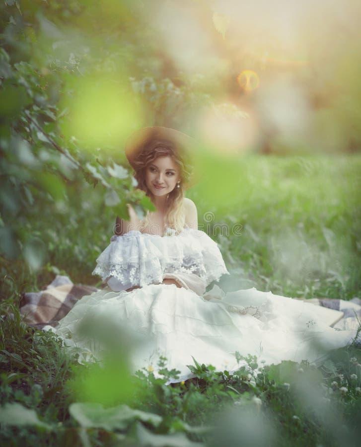Bella ragazza in un vestito bianco che si siede sull'erba fotografia stock