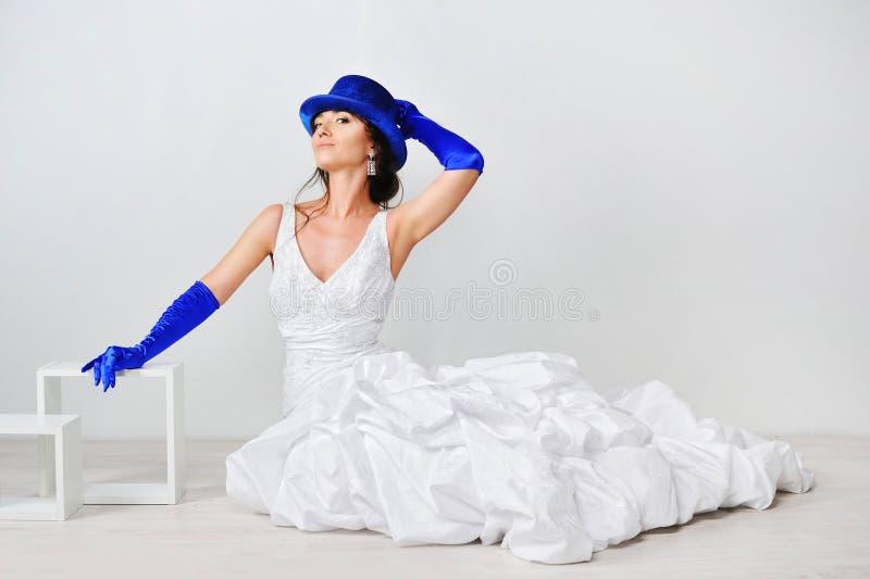 Bella ragazza in un vestito bianco con un cappello blu fotografia stock libera da diritti