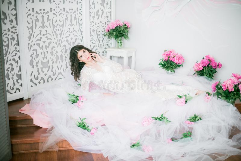 Bella ragazza in un vestito bianco dal pizzo con i fiori della peonia immagine stock libera da diritti