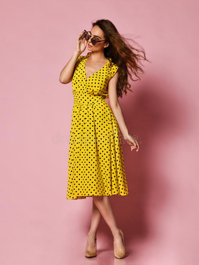 Bella ragazza in un vestito romantico che sorride abbastanza su un fondo porpora Modello femminile riccio snello in un vestito gi immagini stock libere da diritti