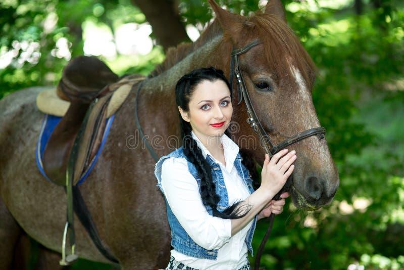 Bella ragazza vicino al cavallo marrone fotografia stock