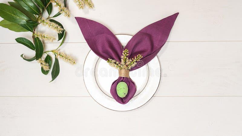 Bella regolazione della tavola di Pasqua con l'uovo, coniglietto di pasqua porpora del tovagliolo, ramo di albero di verde della  fotografia stock libera da diritti