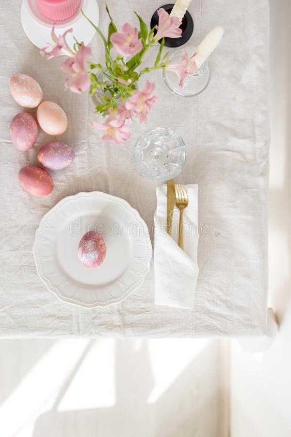 Bella regolazione festiva della tavola di Pasqua con la tovaglia di tela, le uova dipinte ed i fiori fotografia stock libera da diritti