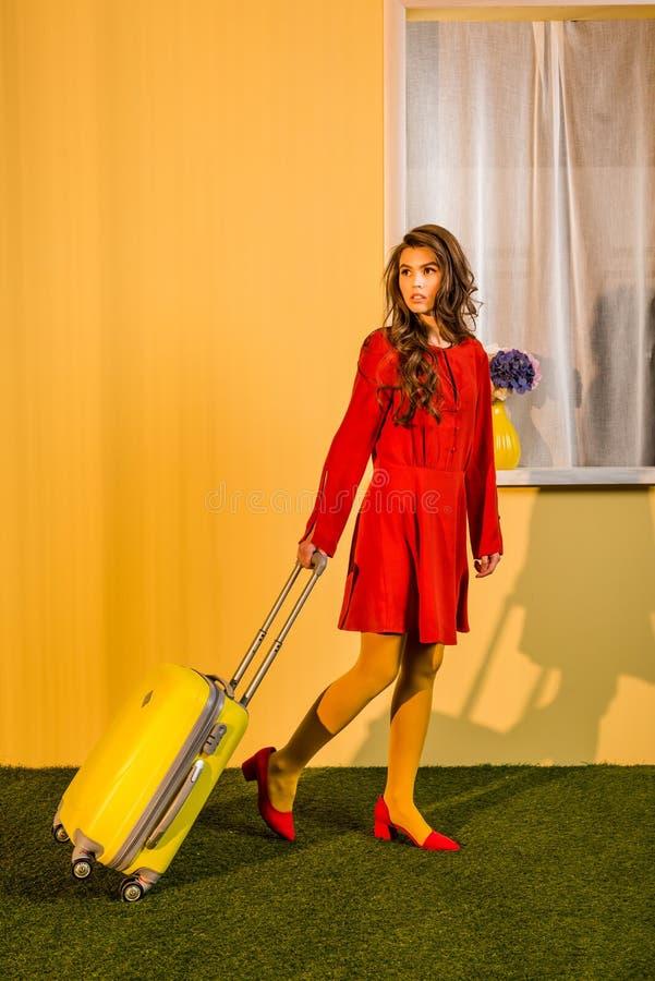 bella retro donna disegnata in vestito rosso che cammina con la valigia a casa immagini stock