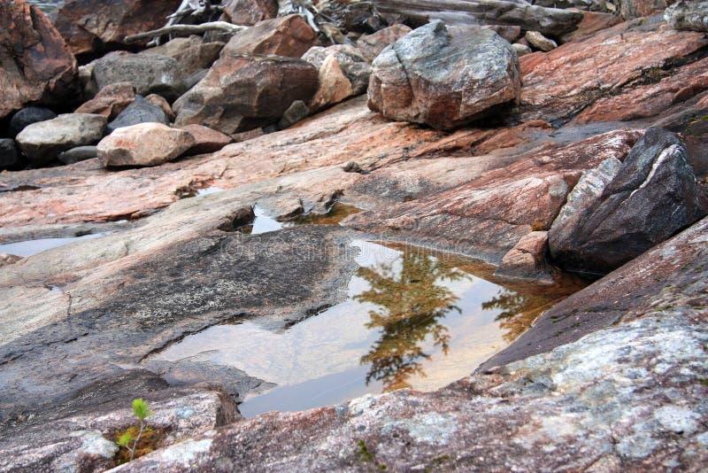 Bella riflessione sulla riva rocciosa immagini stock