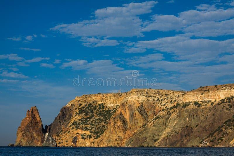 Bella riva del montaggio e mare blu profondo, vista sul mare calmante con le rocce e cielo blu immagine stock libera da diritti