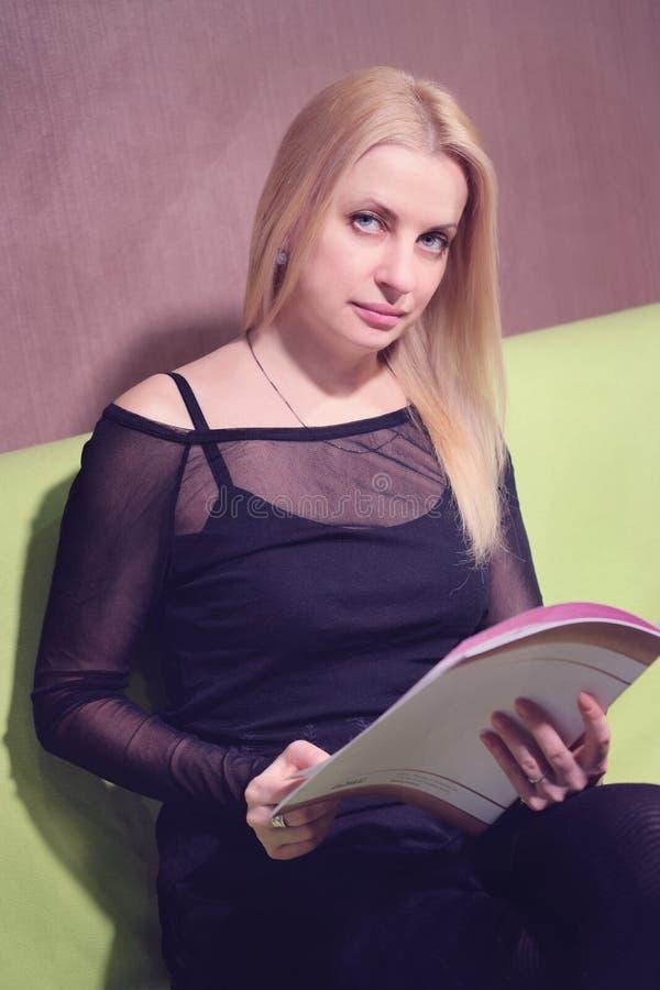 Bella rivista di bellezza della lettura della donna mentre aspettando nella linea nel salone di bellezza fotografia stock libera da diritti