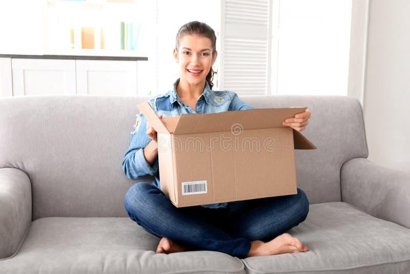 Bella scatola di apertura della giovane donna con il pacchetto fotografie stock