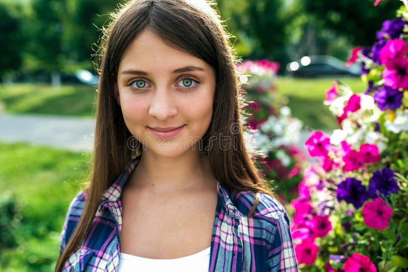 Bella scolara della ragazza 12-15 anni, supporti di estate contro lo sfondo dei fiori Primo piano, emozioni di fotografie stock libere da diritti