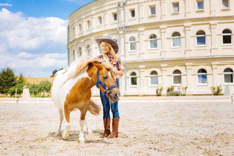 Bella scolara sveglia che cammina con il cavallino sul suo compleanno immagine stock