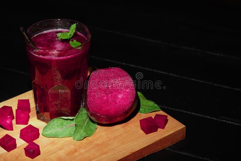 Bella scossa di verdure Frullato della barbabietola su un fondo nero Cubi della barbabietola e foglie dell'insalata su uno scritt fotografie stock