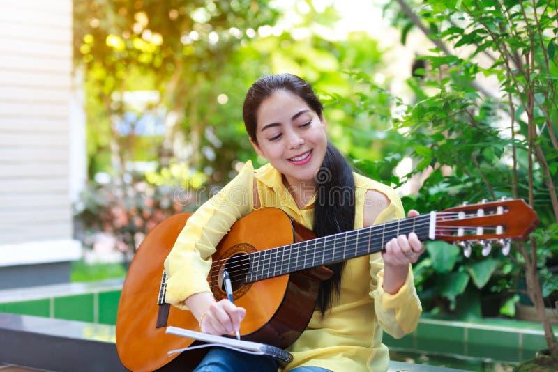 Bella scrittura del cantautore sulla carta per appunti con la chitarra acustica immagini stock libere da diritti