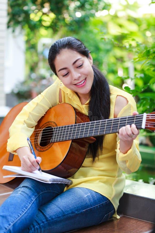 Bella scrittura del cantautore sulla carta per appunti con la chitarra acustica fotografie stock libere da diritti