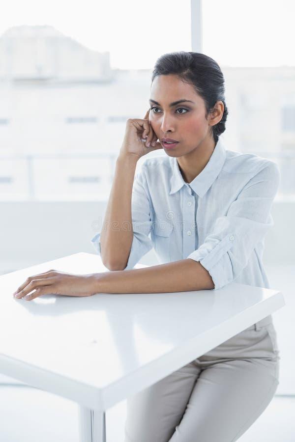 Bella seduta calma della donna di affari premurosa allo scrittorio fotografia stock