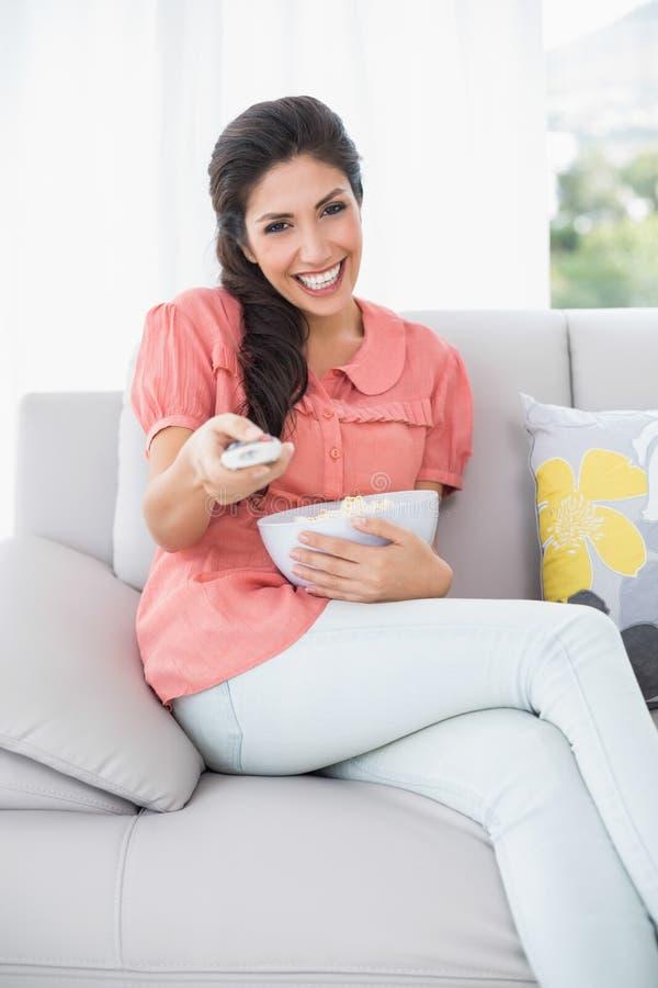 Bella seduta castana sul suo sofà che guarda TV immagini stock