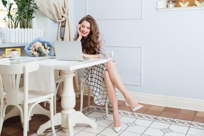 Bella seduta sorridente della giovane donna e computer portatile usando in caffè fotografie stock