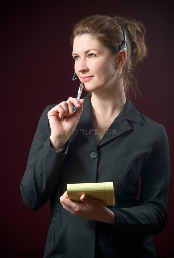 Bella segretaria Wearing Headset Taking Notes immagini stock libere da diritti