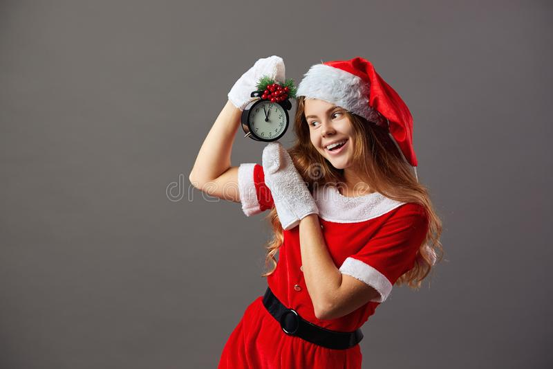 Bella sig Santa Claus ha vestito in rosso l'abito, il cappello di Santa ed i guanti bianchi sta tenendo un orologio a cui mostra  immagini stock libere da diritti