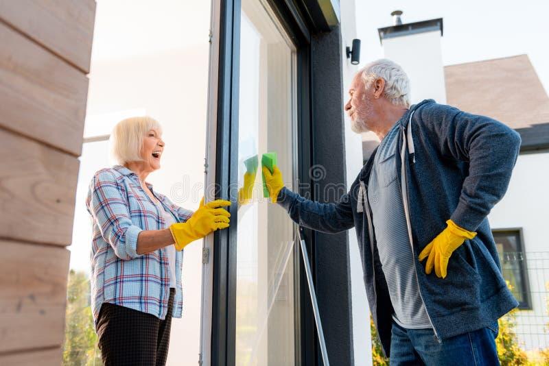 Bella signora anziana che ritiene positiva mentre pulendo le porte con il suo marito immagini stock
