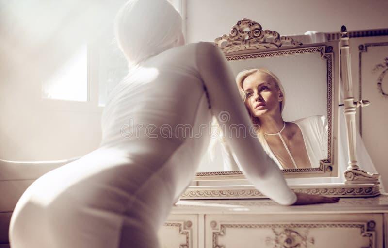 Bella signora bionda alla tavola vestentesi fotografie stock