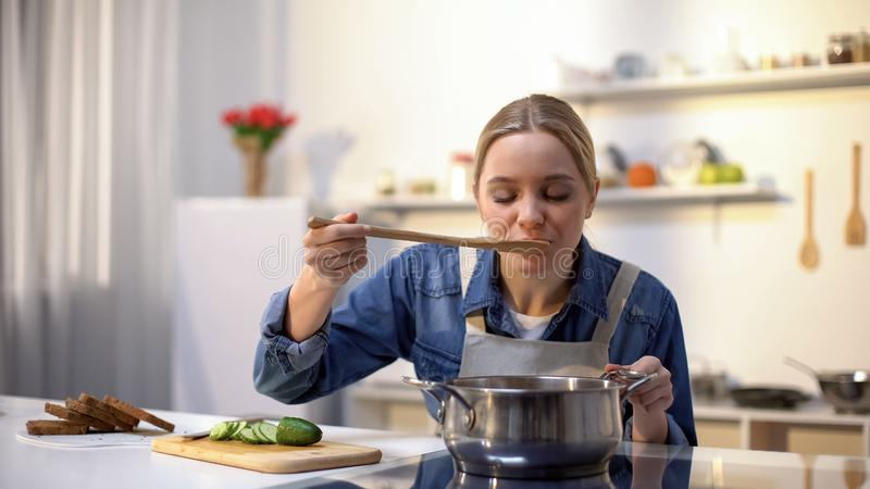 Bella signora che assaggia minestra mentre cucinando, preparando alimento per la cena, stante a dieta immagine stock