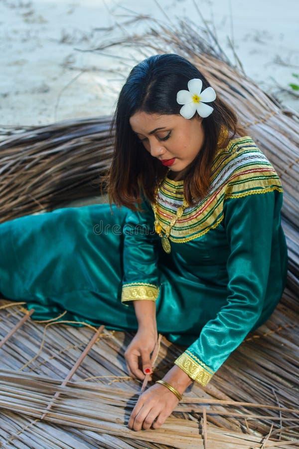 Bella signora delle Maldive in vestito nazionale che fa gli strati per il tetto fotografie stock