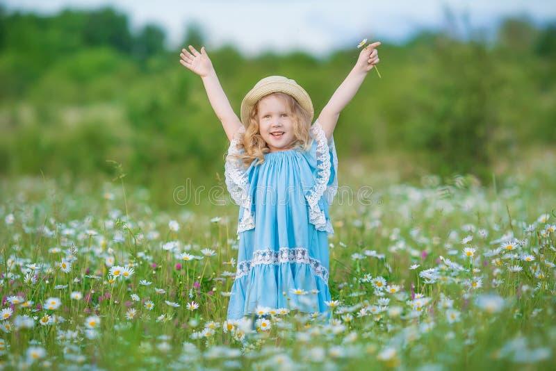Bella signora eccezionale della ragazza sul giacimento di fiori della margherita che gode del tempo di molla di estate con anima  fotografia stock libera da diritti
