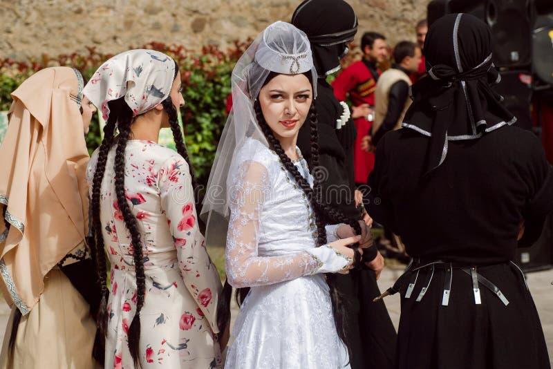 Bella signora georgiana in retro vestito tradizionale che guarda la gente in folla degli eventi durante il festival immagine stock libera da diritti