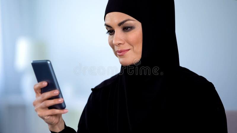 Bella signora musulmana che guarda video online sullo smartphone, tecnologia moderna immagine stock libera da diritti