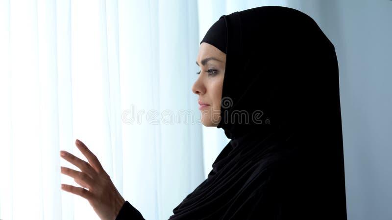 Bella signora musulmana nel marito aspettante del hijab vicino alla finestra, obbedienza islamica fotografia stock libera da diritti