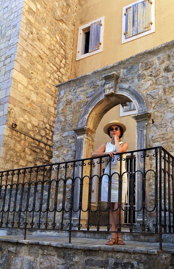 Bella signora in un cappello di paglia sui precedenti dell'arco antico openwork immagini stock