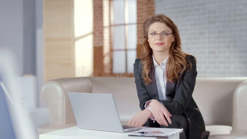 Bella signora in vetri che considera macchina fotografica, corsi online, istruzione a distanza fotografia stock libera da diritti